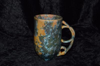 Tasse avec anse ronde en grès orange cristaux verts-gris